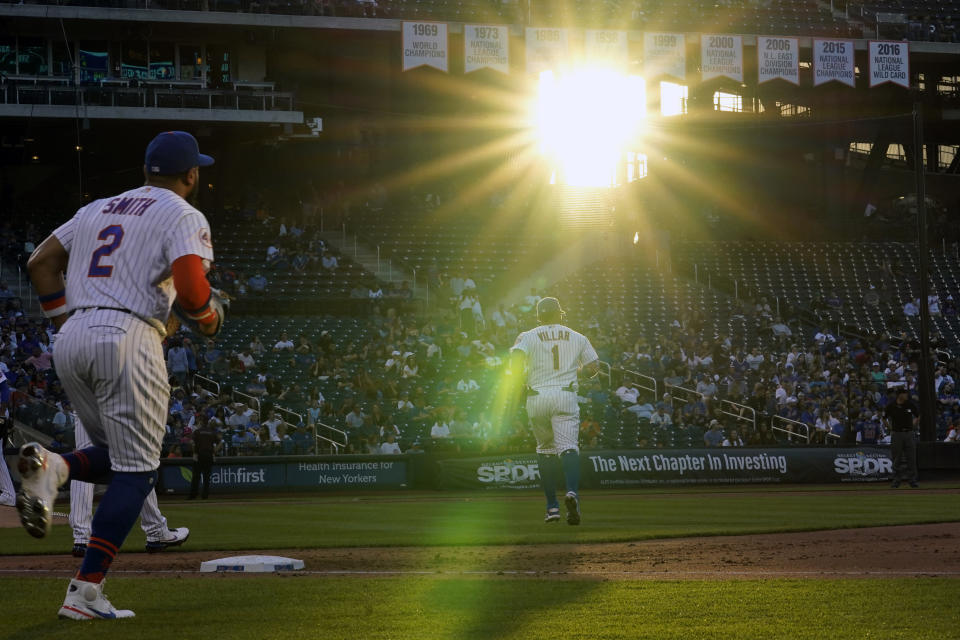 New York Mets players, including Dominic Smith (2) left, and Mets third baseman Jonathan Villar (1) take their positions during a baseball game against the Chicago Cubs as sun streams into the stadium, Thursday, June 17, 2021, in New York. (AP Photo/Kathy Willens)