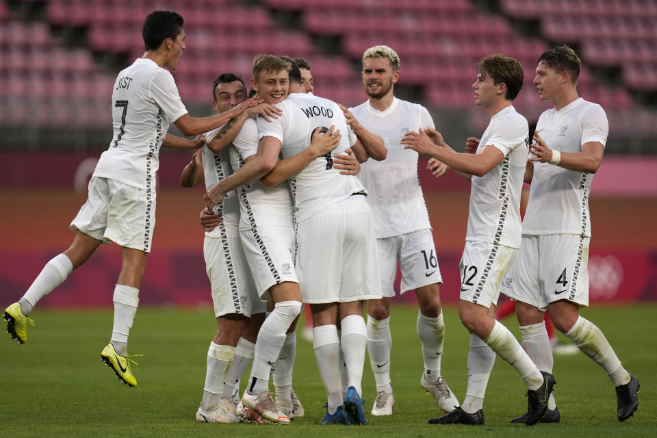 New Zealand's Chris Wood, center, celebrates with teammates after scoring the opening goal against South Korea during a men's soccer match at the 2020 Summer Olympics, Thursday, July 22, 2021, in Kashima, Japan. (AP Photo/Fernando Vergara)