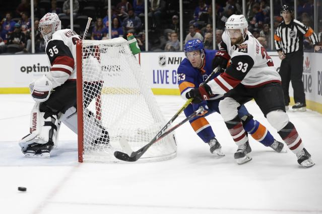 Arizona Coyotes' Alex Goligoski (33) passes the puck away from New York Islanders' Casey Cizikas (53) as Coyotes goaltender Darcy Kuemper (35) watches during the second period of an NHL hockey game Thursday, Oct. 24, 2019, in Uniondale, N.Y. (AP Photo/Frank Franklin II)
