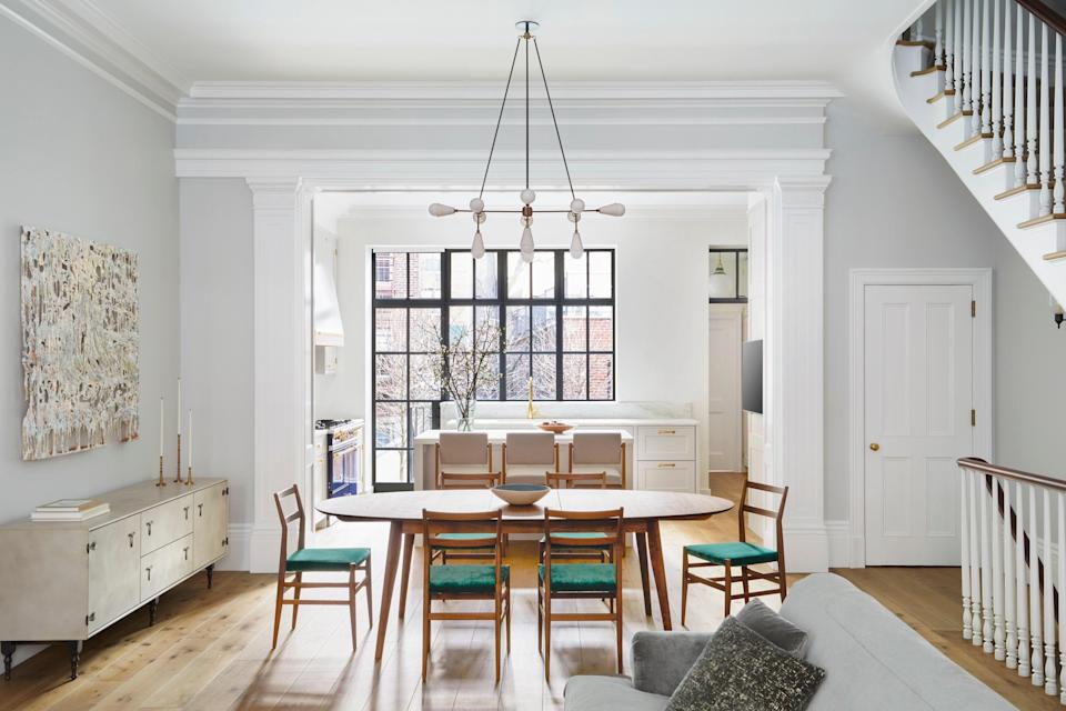 """""""Fitting an essentially totally open parlor floor plan together with traditionally defined rooms and all of the details that go with that was a problem that we feel we successfully solved,"""" says Roberts of the airy, informal design. The dining room features a custom table by Pinch Design, Cassina chairs, and an Apparatus pendant."""