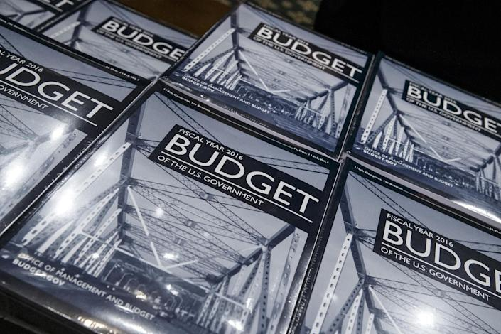 President Barack Obama's new $4 trillion budget plan is distributed by Senate Budget Committee staffer Eric Chalmers as it arrives on Capitol Hill in Washington, early Monday, Feb. 2, 2015. (AP Photo/J. Scott Applewhite)