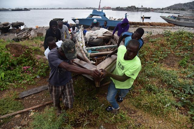<p>Fishermen move a boat inland as Hurricane Irma approaches Cap-Haitien, on Sept. 7, 2017. The fishermen were not aware of Irma. Irma was expected to hit the northern edges of the Dominican Republic and Haiti later Thursday, continuing past eastern Cuba before veering north towards Florida. (Photo: Hector Retamal/AFP/Getty Images) </p>