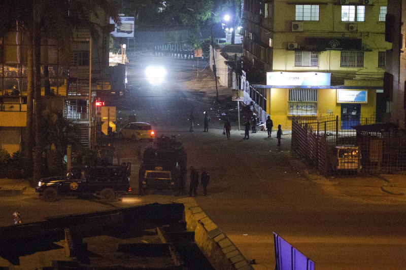 Congolese riot police take position around the electoral commission building at night in Kinshasa, Congo, Tuesday Jan. 8, 2019. As Congo anxiously awaits the outcome of the presidential election, many in the capital say they are convinced that the opposition won and that the delay in announcing results is allowing manipulation in favor of the ruling party. (AP Photo/Jerome Delay)