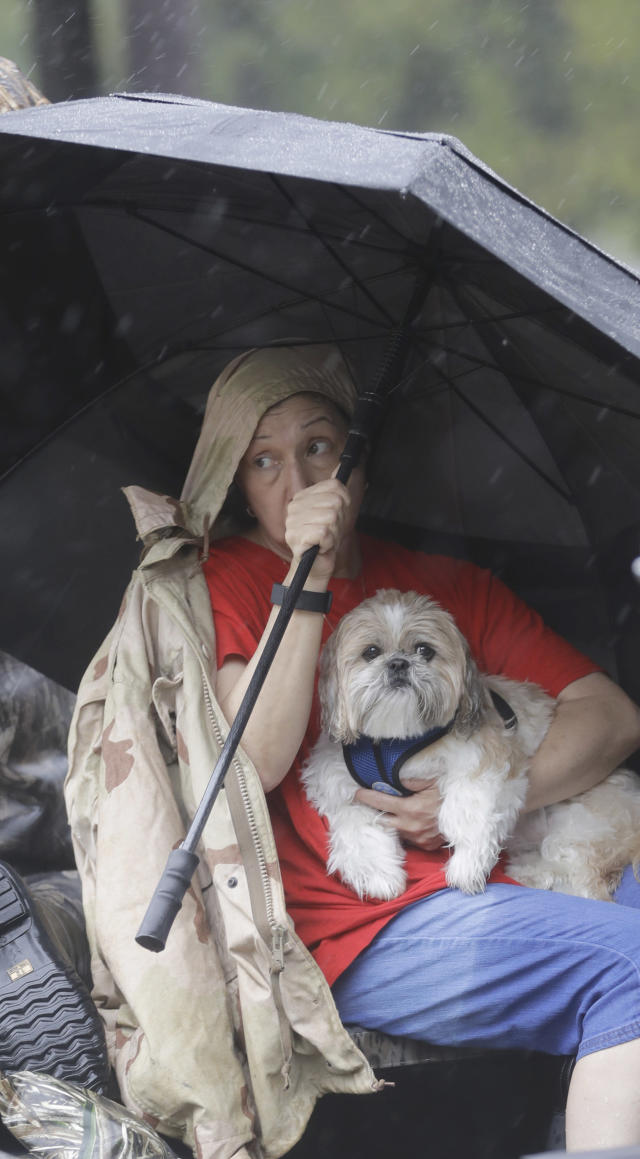 <p>Tina Cross holds her dog Mitzy while being evacuated from her flooded home as floodwaters from Tropical Storm Harvey rise Monday, Aug. 28, 2017, in Spring, Texas. (Photo: David J. Phillip/AP) </p>