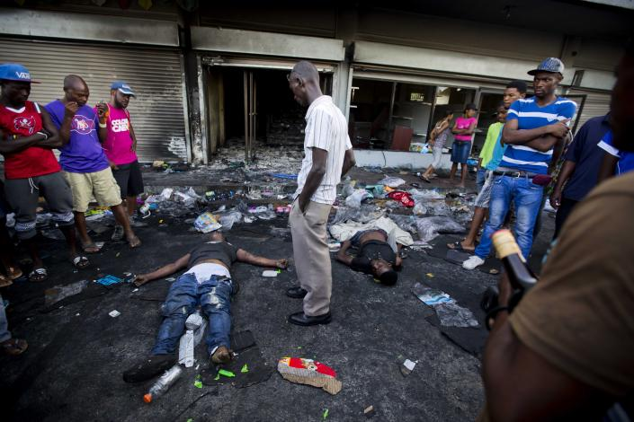 <p>The bodies of two men lie outside a burned and looted store, as one of the men's relatives stands between them, after two days of protests against a planned hike in fuel prices in Port-au-Prince, Haiti, Sunday, July 8, 2018. (Photo: Dieu Nalio Chery/AP) </p>