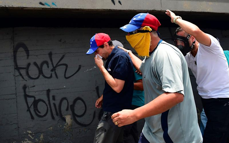 Opposition leader Henrique Capriles (C, wearing cap with Venezuelan colours) looks for refuge under a bridge as police throw tear gas during a rally against Venezuelan President Nicolas Maduro, in the streets of Caracas - Credit: AFP