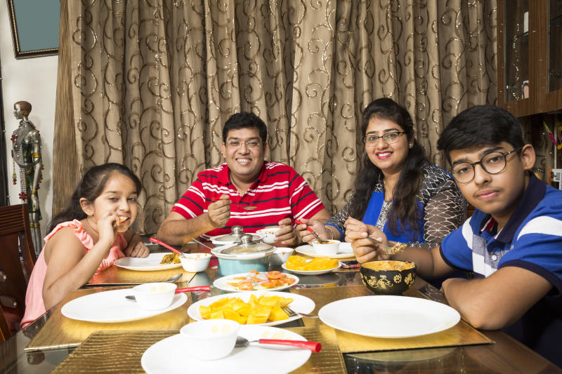 Portrait of a happy family eating together at home - lifestyle concepts