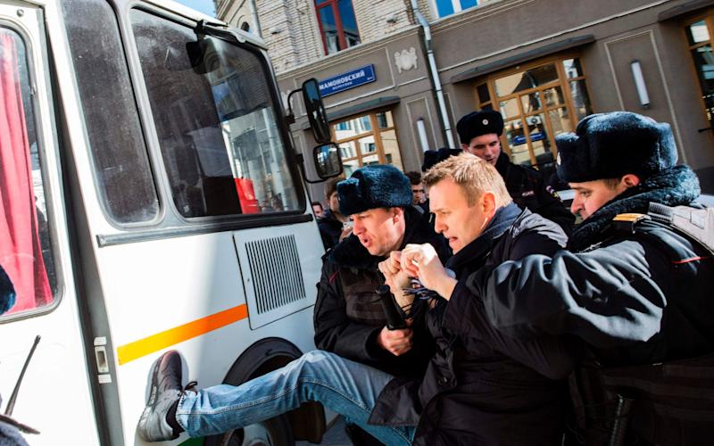 Police officers detain Navalny during yesterday's protests - Credit: AFP