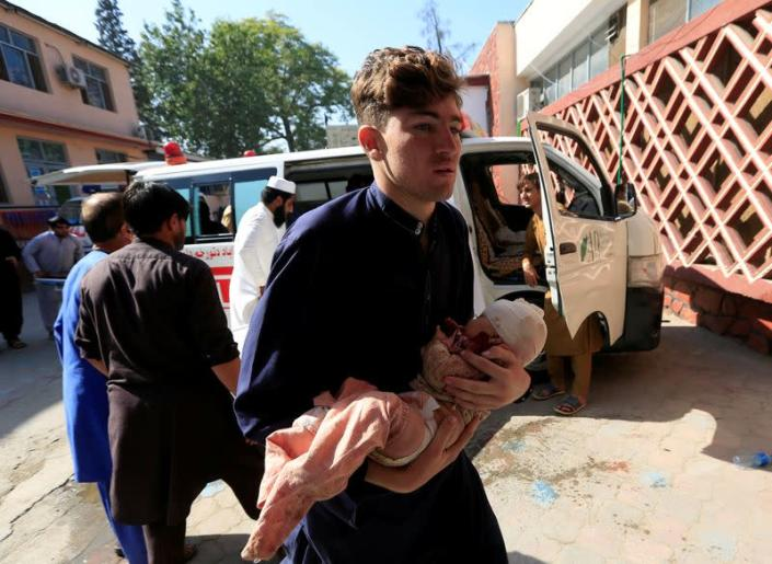 FILE PHOTO: A man carries an injured child at a hospital after a truck bomb blast, in Jalalabad