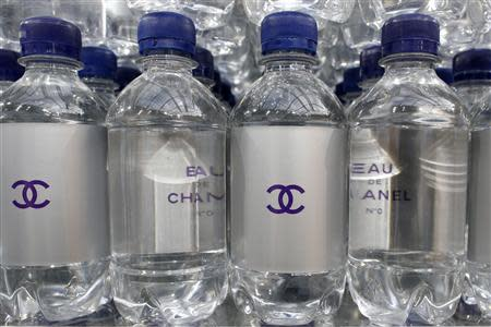 """Chanel mineral bottles are displayed on supermarket shelves at the Grand Palais transformed into a """"Chanel Shopping Center"""" after the German designer Karl Lagerfeld Fall/Winter 2014-2015 women's ready-to-wear collection show for in French fashion house Chanel during Paris Fashion Week March 4, 2014. REUTERS/Benoit Tessier"""