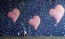 A girl does a cartwheel in front of a mural painted by James Cochran in memory of the victims of the London Bridge attack, on the anniversary of the attack, in London, Britain, June 3, 2018. REUTERS/Simon Dawson