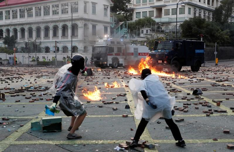 Anti-government protesters throw molotov cocktails towards police vehicles during clashes, outside Hong Kong Polytechnic University