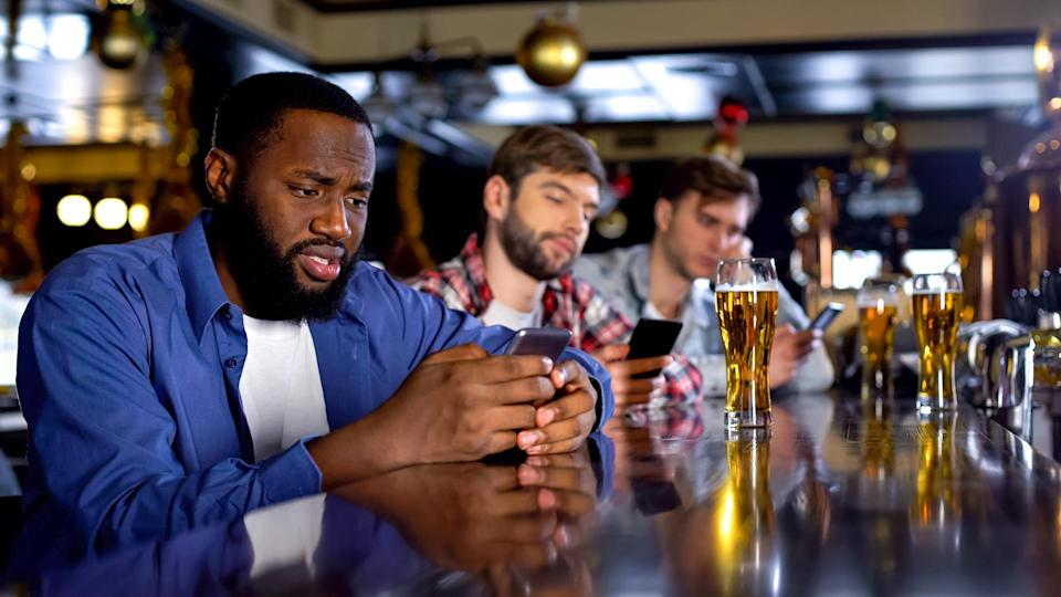 Sad multiethnic men surfing internet on phones in pub instead of communicating.