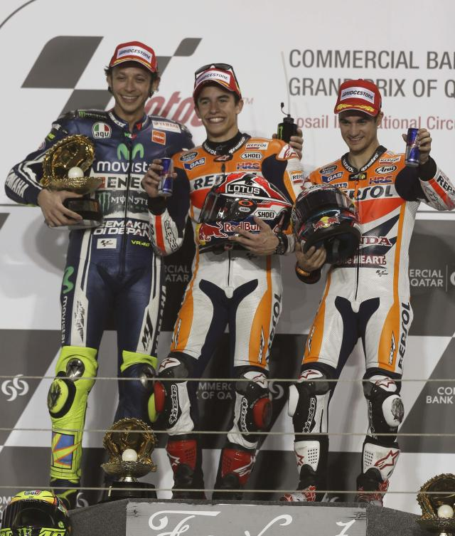 Second placed Yamaha MotoGP rider Valentino Rossi (L) of Italy, winner Honda MotoGP rider Marc Marquez (C) of Spain and third placed, compatriot, team mate Dani Pedrosa stand on the podium after the Qatar MotoGP Grand Prix at the Losail International circuit in Doha March 23, 2014. REUTERS/Stringer (QATAR - Tags: SPORT MOTORSPORT)