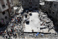 People gather near the rubble of destroyed residential building which was hit by Israeli airstrikes, in Beit Lahiya, Gaza Strip, Thursday, May 20, 2021. (AP Photo/Adel Hana)