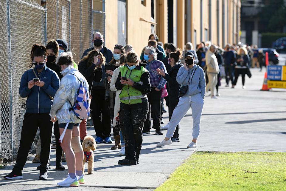 People are seen waiting in line outside of the Palais Theatre at a pop-up Covid19 testing facility in St Kilda. Source: AAP