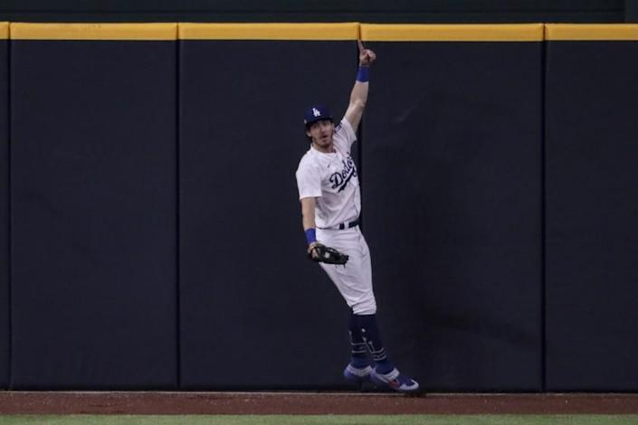 """Dodgers center Cody Bellinger celebrates after making a catch to prevent a home run by San Diego's Fernando Tatis Jr. during the seventh inning of Game 2 of the NLDS on Wednesday. <span class=""""copyright"""">(Robert Gauthier / Los Angeles Times)</span>"""