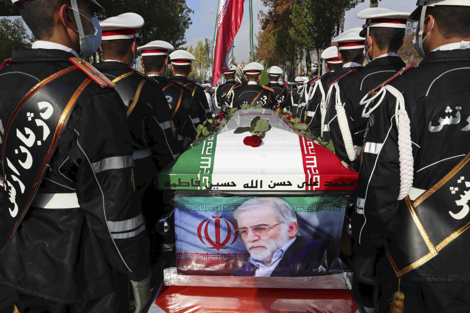 """In this photo released by the official website of the Iranian Defense Ministry, military personnel stand near the flag-draped coffin of Mohsen Fakhrizadeh, a scientist who was killed on Friday, during a funeral ceremony in Tehran, Iran, Monday, Nov. 30, 2020. Fakhrizadeh founded Iran's military nuclear program two decades ago, and the Islamic Republic's defense minister vowed to continue the man's work """"with more speed and more power."""" (Iranian Defense Ministry via AP)"""