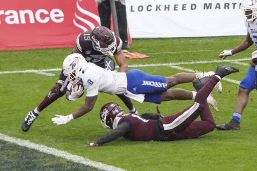 Tulsa running back Deneric Prince (8) dives past the goal line for a touchdown in between Mississippi State safety Collin Duncan (19) and safety Shawn Preston Jr. (12) during the second half of the Armed Forces Bowl NCAA college football game Thursday, Dec. 31, 2020, in Fort Worth, Texas. (AP Photo/Jim Cowsert)