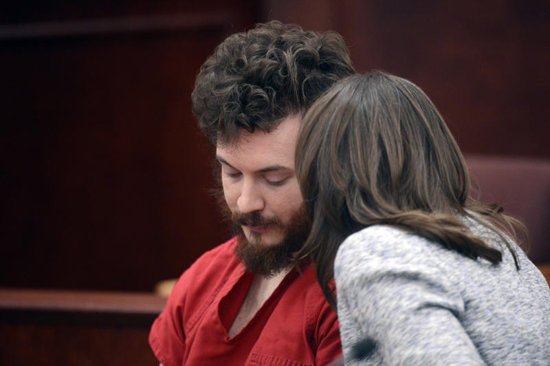 Defense attorney Tamara Brady talks to defendant James Holmes during his arraignment in Centennial, Colo., on Tuesday, March 12, 2013. Judge William Blair Sylvester entered a not guilty plea on behalf of James Holmes on Tuesday after the former graduate student's defense team said he was not ready to enter one. (AP Photo/Denver Post, RJ Sangosti, Pool)