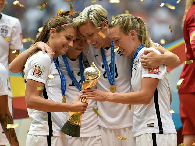 Alex Morgan #13, Lauren Holiday #12, Abby Wambach #20 and Whitney Engen #6 of the United States of America hold the World Cup Trophy after their 5-2 win over Japan in the FIFA Women's World Cup Canada 2015 Final at BC Place Stadium on July 5, 2015 in Vancouver, Canada. | Rich Lam—Getty Images