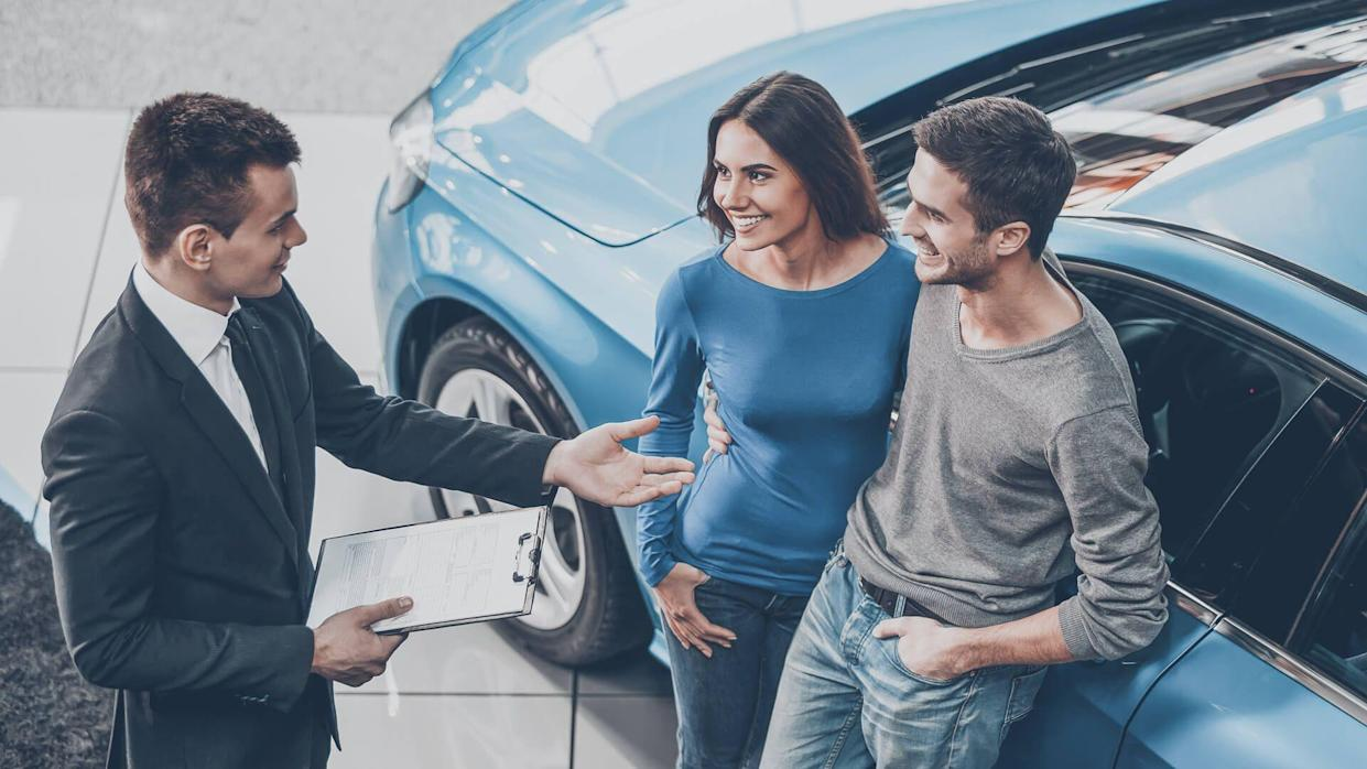 car dealership agent with couple