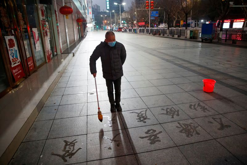 A man wears a face mask as he practices calligraphy of Chinese characters on a pavement in Jiujiang