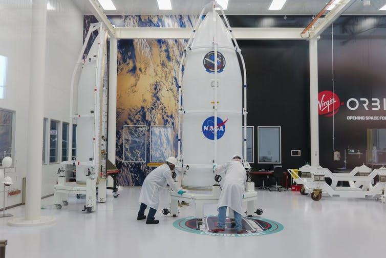 The NASA payload in a warehouse being inspected by two men.