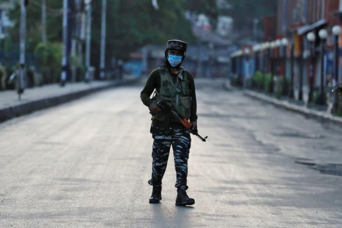 An Indian Central Reserve Police Force officer patrols on an empty street during a lockdown on the first anniversary of the revocation of Kashmir's autonomy in Srinagar