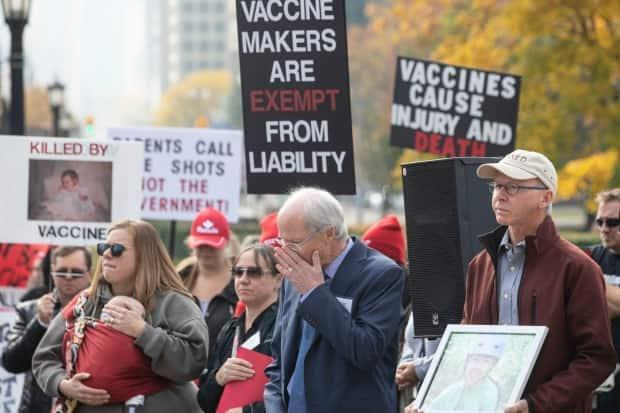 Ted Kuntz (centre), director and vice president of Vaccine Choice Canada, joins fellow protesters in observing a minute's silence during a rally against Ontario's vaccination law outside the legislature in Toronto on Oct. 29, 2019. (Chris Young/The Canadian Press - image credit)