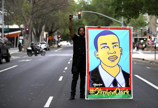 <p>A Black Lives Matter protester holds an illustration of Stephon Clark during a march and demonstration through the streets of Sacramento on April 4, 2018 in Sacramento, Calif. (Photo: Justin Sullivan/Getty Images) </p>