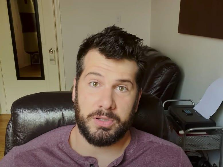 Steven Crowder sitting in a desk chair, looking at the camera with a couch behind him