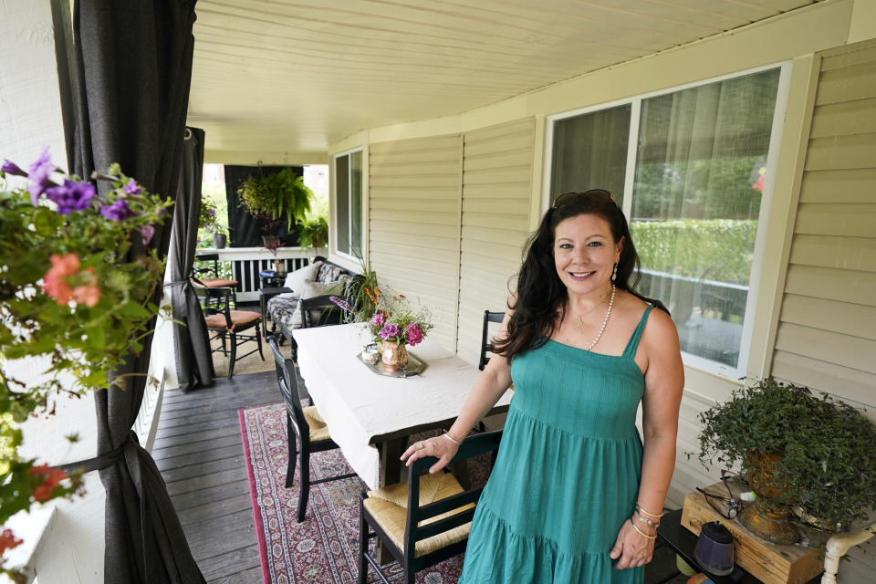 Heather Bise, owner of The House of Bise Bespoke, poses on the front porch where she entertains guests, Monday, July 19, 2021, in Cleveland. Small businesses in the U.S. that depend on tourism and vacationers say business is bouncing back, as people re-book postponed trips and take advantage of loosening restrictions, a positive sign for the businesses that have struggled for more than a year. Bise started in 2019 and catered to international tourists, attracting guests from New Zealand, Botswana, Eastern Europe and elsewhere. (AP Photo/Tony Dejak)