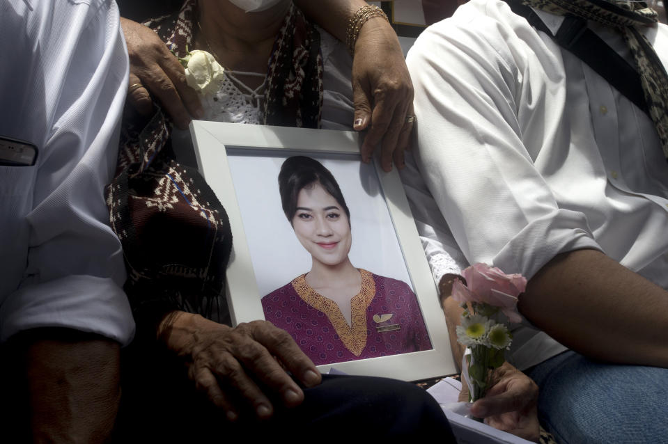 A relative holds a photo of Mia Tresetyani, a victim of the crash of Sriwijaya Air flight SJ-182 during her burial in Denpasar, Bali, Indonesia on Thursday, Jan. 21, 2021. The Indonesian leader on Wednesday reassured relatives of the passengers killed when the plane nosedived into the Java Sea that compensation is paid to family members struggled with grief. (AP Photo/Firdia Lisnawati)