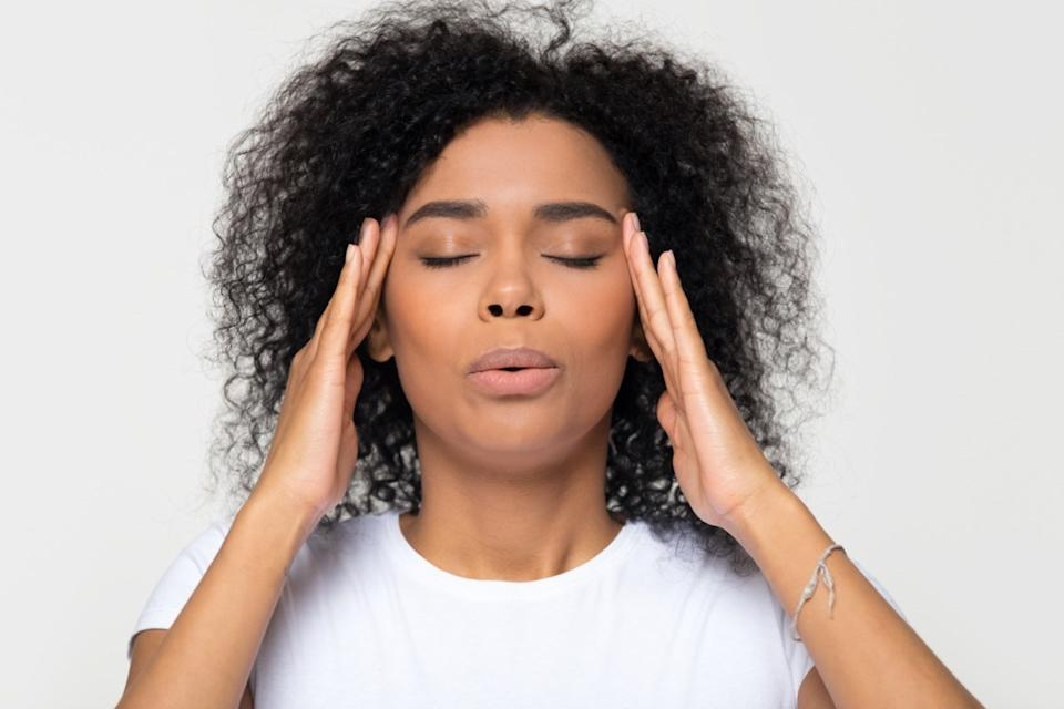 Nervous african woman breathing calming down relieving headache or managing stress, black girl feeling stressed self-soothing massaging temples exhaling