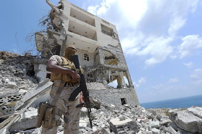 A Saudi soldier stands next to a damaged building in the area of the presidential palace in the southern Yemeni city of Aden on September 27, 2015 (AFP Photo/Ahmed Farwan)