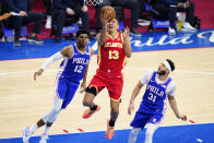 Atlanta Hawks' Bogdan Bogdanovic, center, goes up for a shot between Philadelphia 76ers' Tobias Harris, left, and Seth Curry during the second half of Game 5 in a second-round NBA basketball playoff series, Wednesday, June 16, 2021, in Philadelphia. (AP Photo/Matt Slocum)