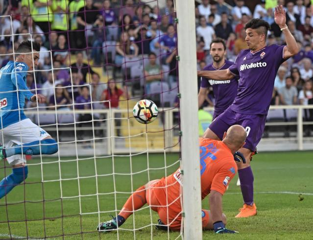 FILE - In this Sunday, April 29, 2018 filer, Fiorentina's Giovanni Simeone, right, scores his side's 2nd goal during the Serie A soccer match between Napoli and Fiorentina, at the Artemio Franchi stadium in Florence, Italy. Nearly 20 years after his father scuppered Juventus' title hopes, Giovanni Simeone has made it up to the Serie A club. Current Atletico Madrid coach Diego Simeone fired Lazio to a 1-0 win against Juventus in April 2000, with the capital club going on to finish a point above the Bianconeri to win the title. On Sunday, 18 years later, the younger Simeone netted a hat trick to help Fiorentina beat Juve's closest challengers Napoli 3-0 and leave the Bianconeri on the brink of a seventh successive title. (Maurizio Degl'Innocenti/ANSA via AP)