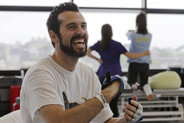 "In this Wednesday, May 22, 2013 photo, Boston Marathon bombing survivor Pete DiMartino, of Rochester, N.Y., smiles during a physical therapy session at the Spaulding Rehabilitation Hospital in Boston. DiMartino was injured in an explosion near the finish line, which blew away much of one leg and burned the other. ""I don't want anybody feeling sorry for me,"" he said. ""... I want people to see that this has made me a better person and I want people to become better people through what they see through me."" (AP Photo/Charles Krupa)"