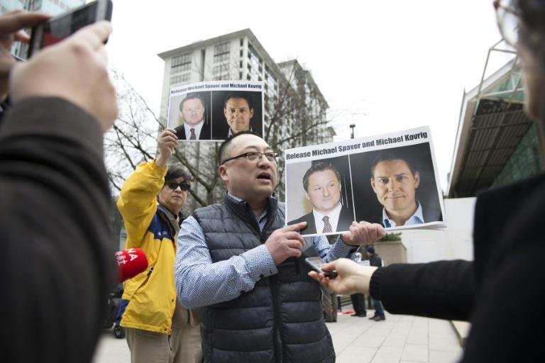 A protestor holds photos of Canadians Michael Spavor and Michael Kovrig, who are being detained by China, outside the Vancouver extradition hearing for Huawei executive Meng Wanzhou