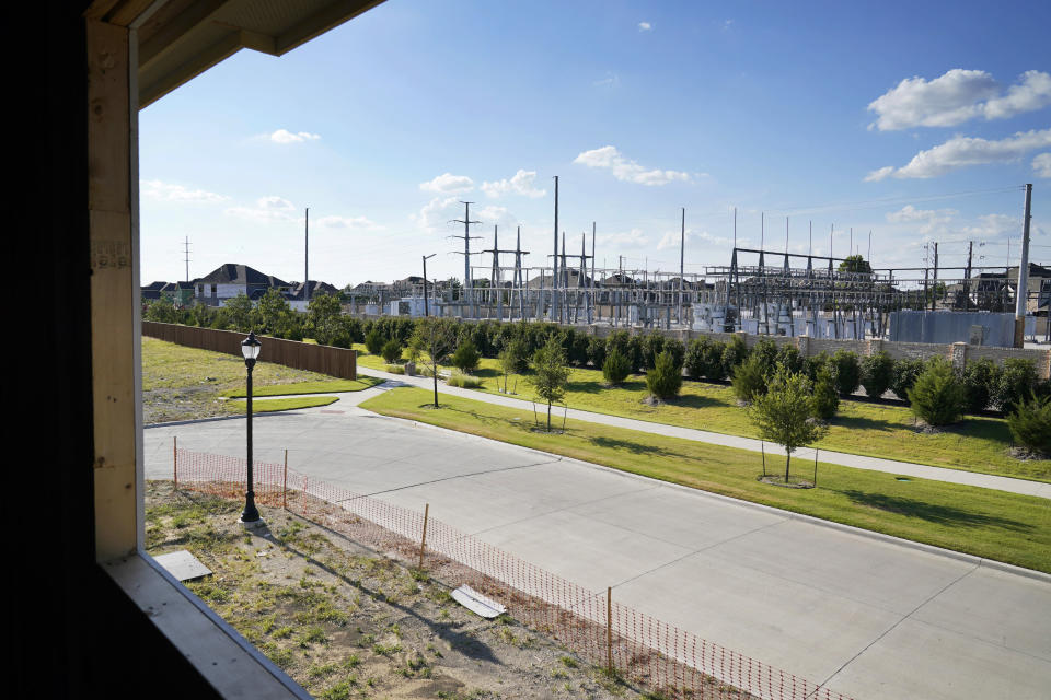 A electrical power grid, right rear, is seen outside the window and across the street of a home under construction in a new subdivision in Frisco, Texas, Thursday, Aug. 12, 2021. The once-a-decade battle over redistricting is set to be a showdown over the suburbs, as new census data released Thursday showed rapid growth around the some of the nation's largest cities and shrinking population in many rural counties. (AP Photo/Tony Gutierrez)
