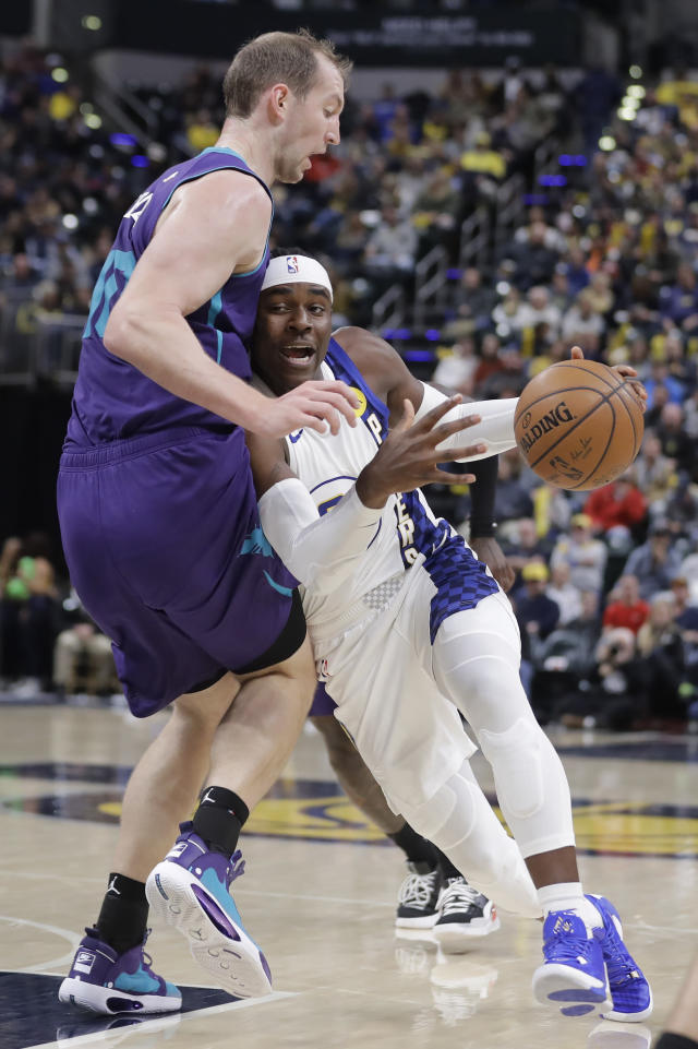 Indiana Pacers' Aaron Holiday, right, drives to the basket against Charlotte Hornets' Cody Zeller, left, during the second half of an NBA basketball game, Sunday, Dec. 15, 2019, in Indianapolis.(AP Photo/Darron Cummings)