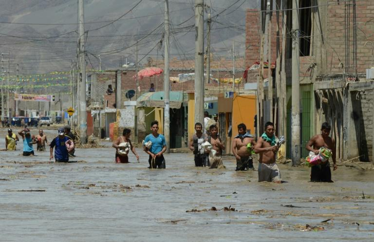 Residents of the town of Huarmey, 300 km north of Lima, wade through muddy water in the street after a flash flood hit the area the night before