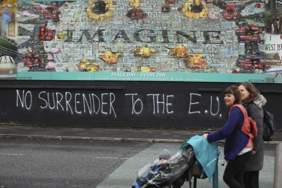 """FILE - In this Monday Oct. 14, 2019 file photo people walk past pro-Brexit graffiti in West Belfast Northern Ireland. The chaotic scenes during a week of violence on the streets of Northern Ireland have stirred memories of decades of Catholic-Protestant conflict, known as """"The Troubles."""" A 1998 peace deal ended large-scale violence but did not resolve Northern Ireland's deep-rooted tensions. (AP Photo/Peter Morrison, File)"""