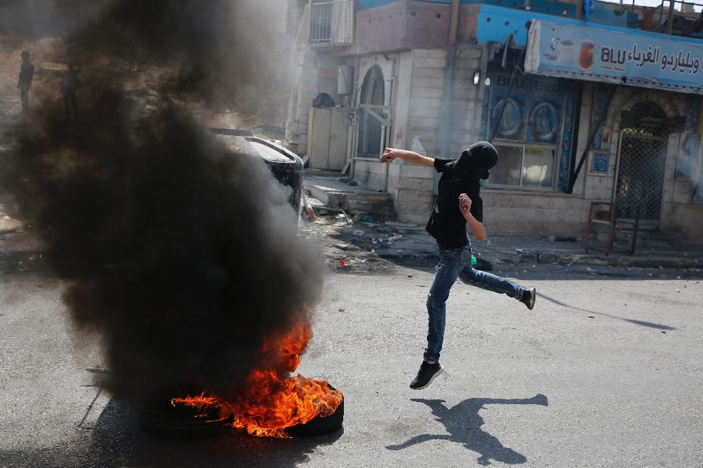 A masked Palestinian throws a stone towards Israeli troops during a protest on May 22, 2017 in support of prisoners on hunger strike in Israeli jails for more than a month and denouncing a visit by US President Donald Trump (AFP Photo/ABBAS MOMANI)