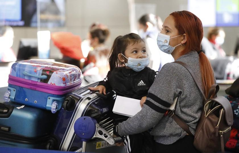 LOS ANGELES, CA - NOVEMBER 16: Passenger Karen Alvarez comforts her 3-year-old daughter Mercedez Gomez as they wait in line at the Tom Bradley International Terminal at LAX before their flight to Nicaragua on Monday November 16, 2020 as weekly coronavirus cases have doubled in just the last month around the state, and Los Angeles County had the grim distinction of recording more than 6,800 cases this weekend alone, an alarming spike that has officials talking about more restrictions. California officials are urging those who do head out of state to self-quarantine for 14 days when they return. LAX Los Angeles Airport on Monday, Nov. 16, 2020 in Los Angeles, CA. (Al Seib / Los Angeles Times