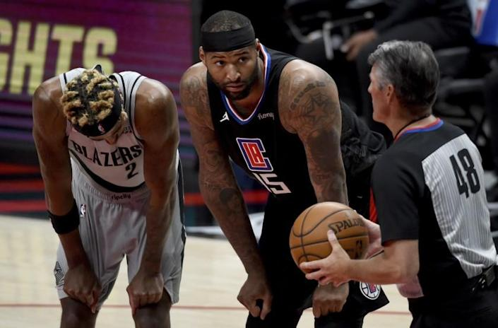 Los Angeles Clippers center DeMarcus Cousins, center, talks with official referee Scott Foster, right, as Portland Trail Blazers forward Rondae Hollis-Jefferson, left, listens during the second half of an NBA basketball game in Portland, Ore., Tuesday, April 20, 2021. The Clippers won 113-112. (AP Photo/Steve Dykes)