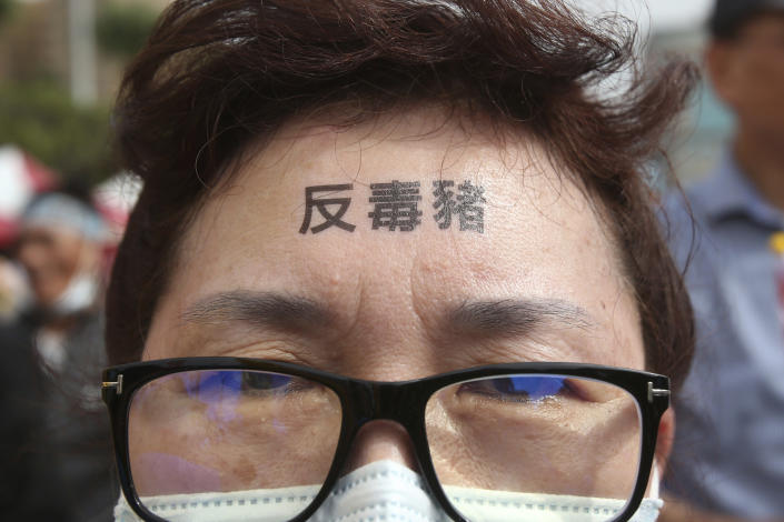 """A participant has a slogan """"Anti-poisoned pork"""" written on her forehead during a protest in Taipei, Taiwan, Sunday, Nov. 22. 2020. Thousands of people marched in streets on Sunday demanding the reversal of a decision to allow U.S. pork imports into Taiwan, alleging food safety issues. (AP Photo/Chiang Ying-ying)"""