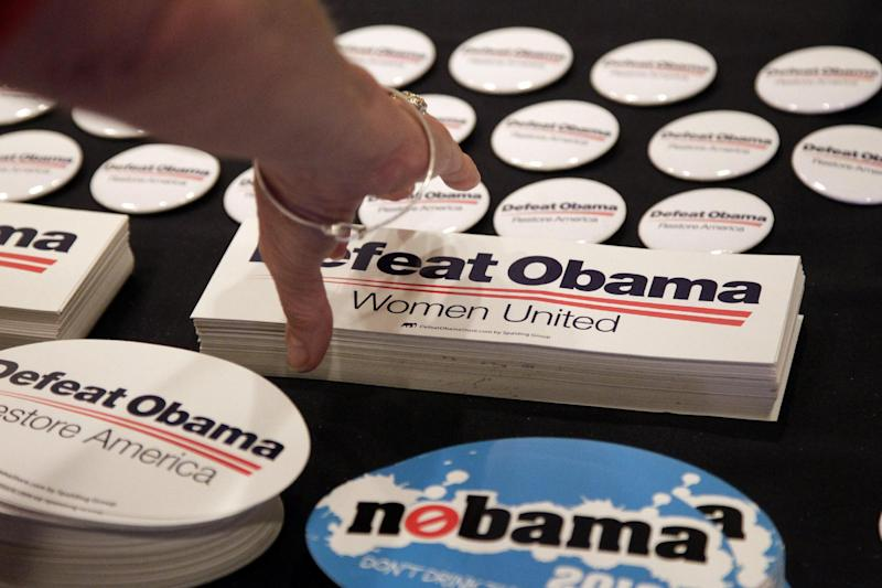 A woman reaches for a bumper sticker at the RNC State Chairman's National Meeting in Scottsdale, Ariz., Friday, April 20, 2012. Republican presidential candidate, former Massachusetts Gov. Mitt Romney is scheduled to speak at the meeting. (AP Photo/Jae C. Hong)