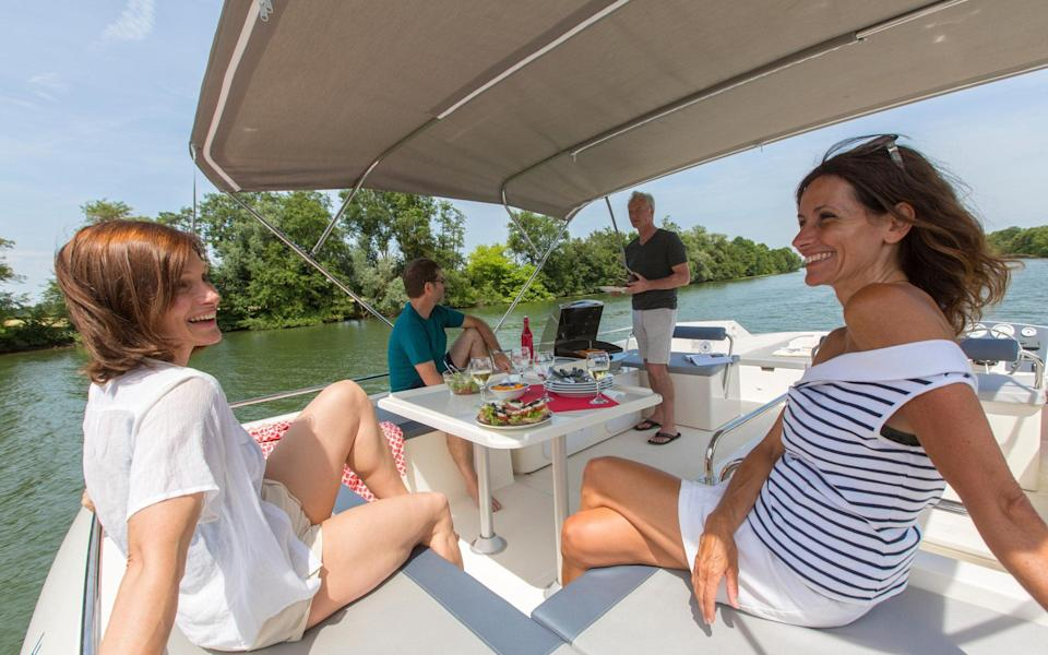 Four people on boat eating meal - Le Boat